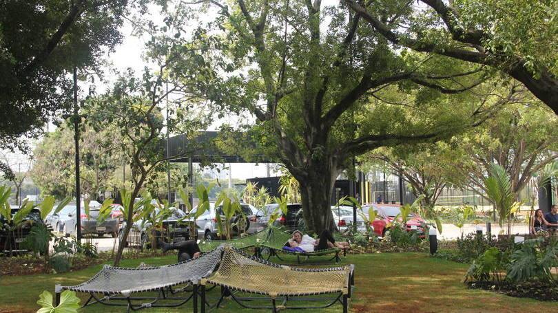 jardim da sede do mercado livre em SP. Na foto, um grande gramado com árvores e redes para descansar.