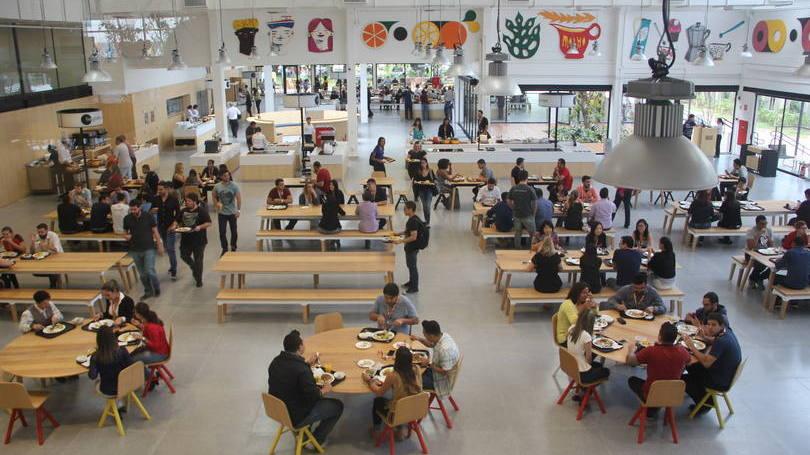 refeitório no mercado livre. Na foto, um espaço amplo repleto de pessoas sentadas em mesas retangulares.