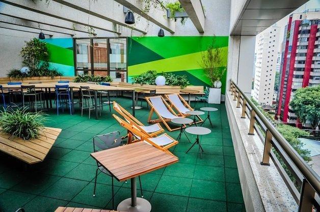 espaço ao ar livre no campus do google em são paulo. Há mesas e cadeiras para relaxar e fazer networking