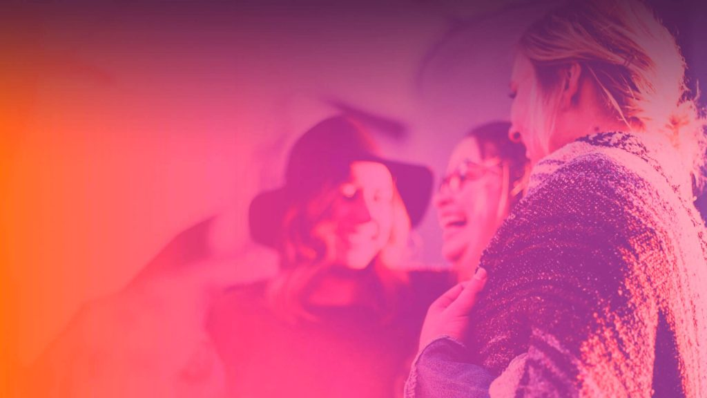 foto com três mulheres sorrindo. ela tem um fundo rosa