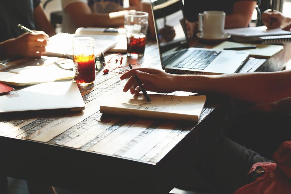 imagem que mostra uma mão sobre uma mesa com um lápis e um caderno. Na mesa, há também computadores.