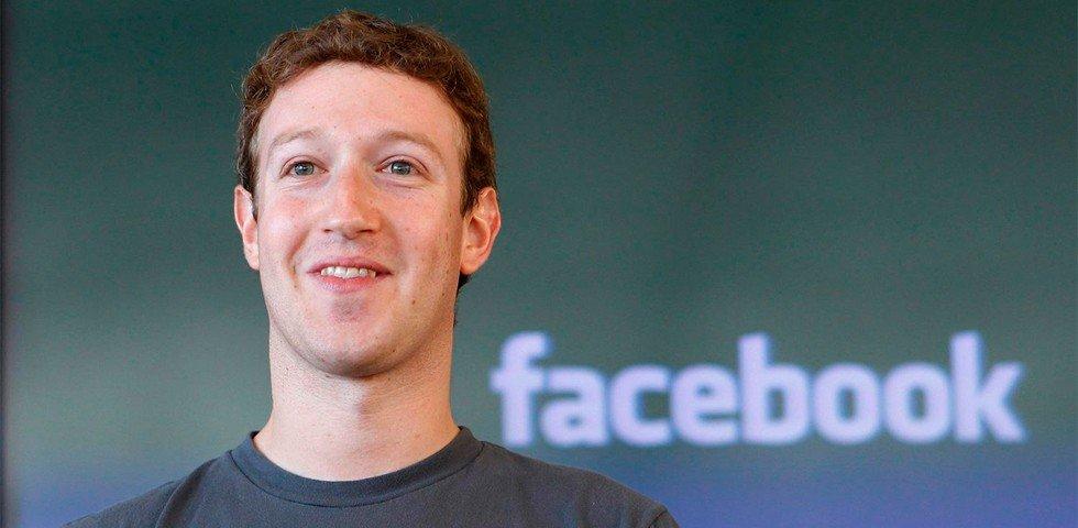 Na foto está Mark Zuckerberg, CEO e fundador do Facebook, com camisa cinza. Ele sorri! Atrás dele, está o logo do Facebook em branco.