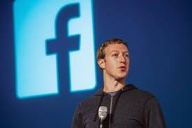 Na foto, Mark Zuckerberg, CEO e fundador do Facebook, está em um evento. Ele veste moleton cinza-escuro. Ele está em um lugar, tipo um auditório, que apresenta um fundo iluminado em azul-escuro.