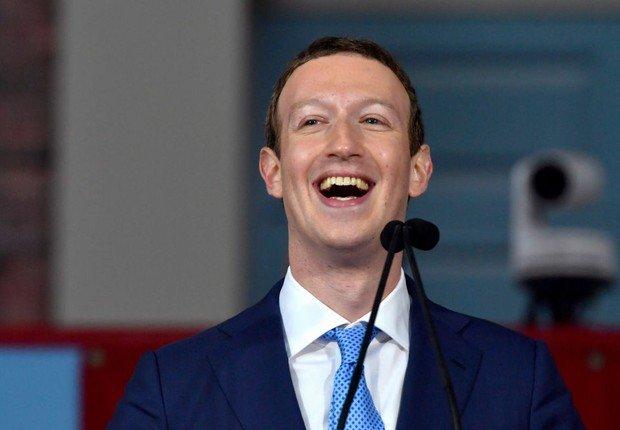 Nestaf foto, Mark Zuckerberg, CEO e fundador do Facebook, veste um terno azul e gravata azul-claro com listrar brancas. Ele dá um sorriso de alegria.