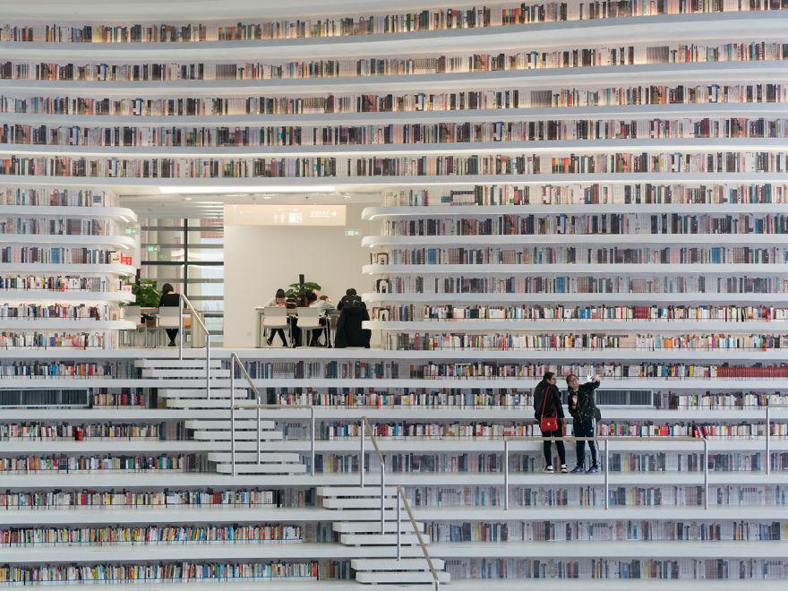 Biblioteca de Binhai, na China. A biblioteca tem 200 mil livros. A foto mostra várias estantes com livro. As estantes são brancas e o contraste é muito bonito. Há pessoas na foto, pesquisando livro.